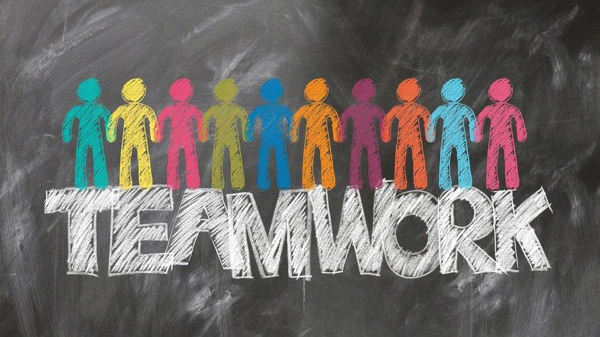 Zu sehen sind bunte Kreide-Figuren und ein Zahnrad an einer Wandtafel mit dem Überschrift Teamwork.