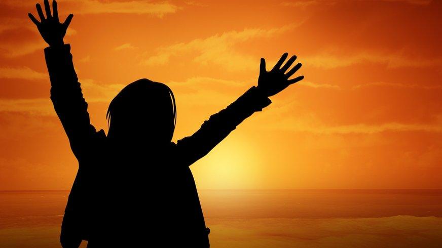 Eine Person ist im Sonnenuntergang zu sehen. Sie nimmt begeistert die Arme hoch.