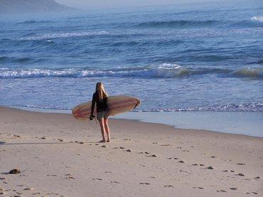 Mädchen mit Surfboard am Strand